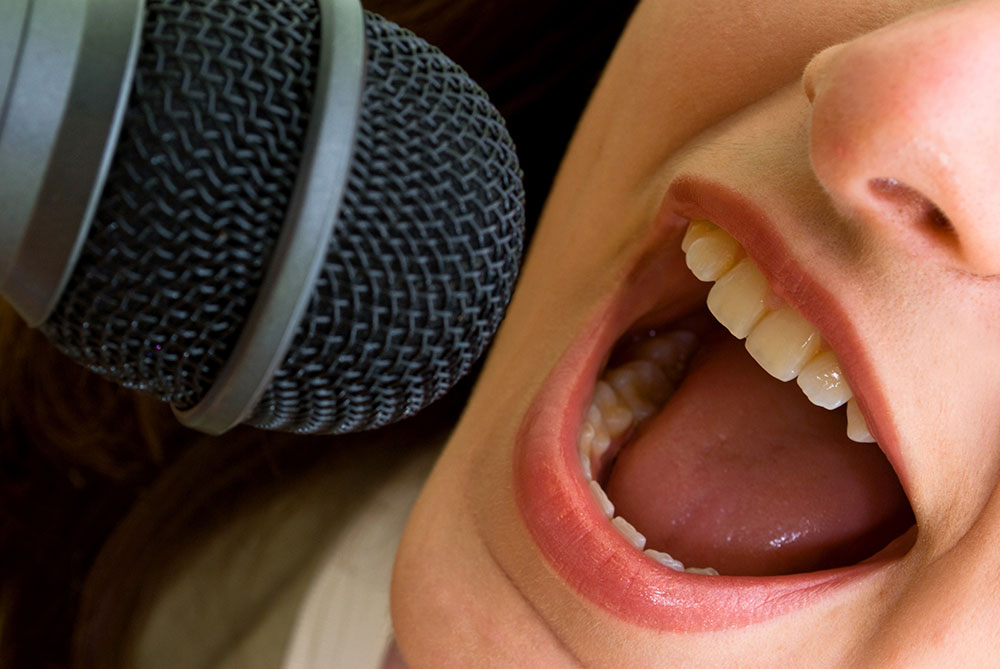 口を大きく開けて歌う女性