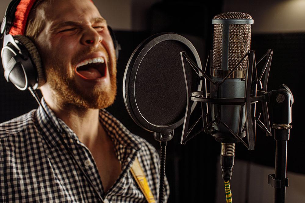 力いっぱいシャウトして歌う男性