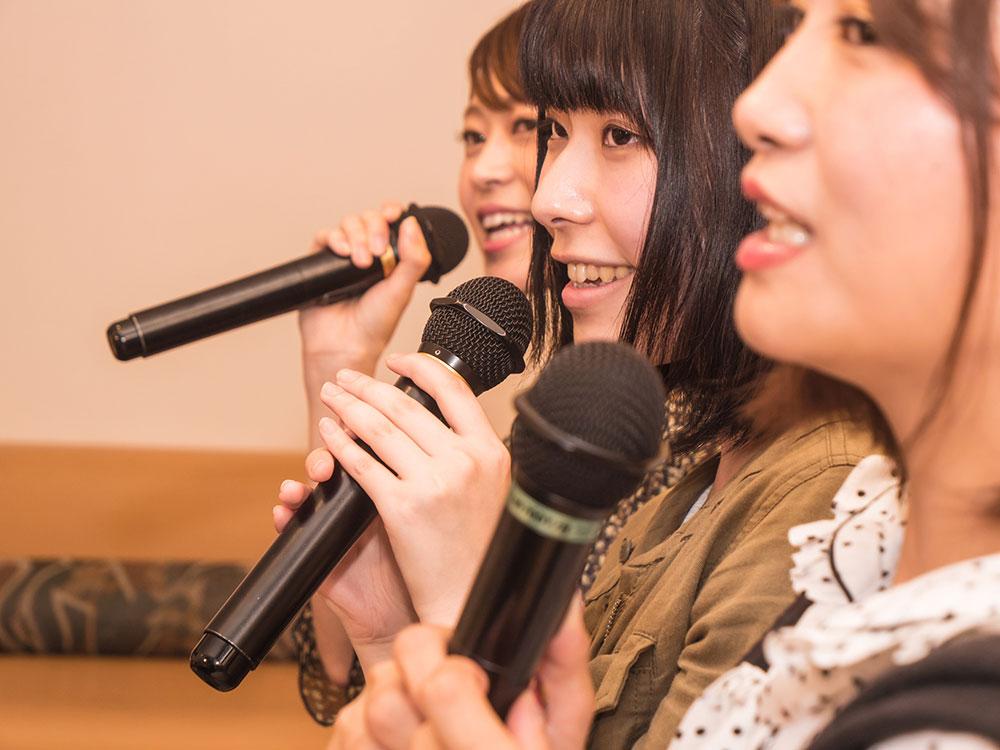 カラオケでマイクを持って歌う3人の女声