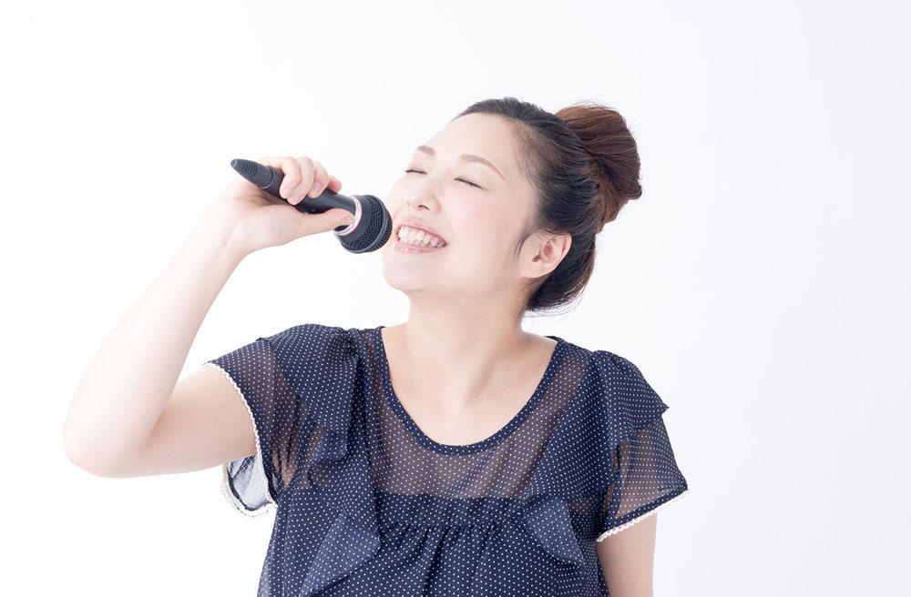マイクを持って少し顔を上に向けて歌う女性