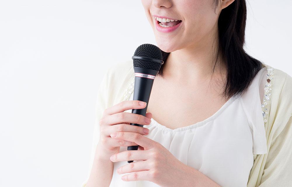 マイクを縦に持って歌う女性